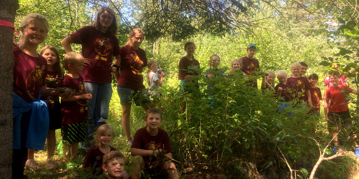 several elementary aged children and two chaperones out in the woods