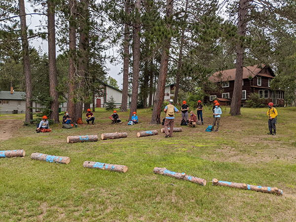 logs laid out on the ground with students lined up looking at them and listening to an instructor speak