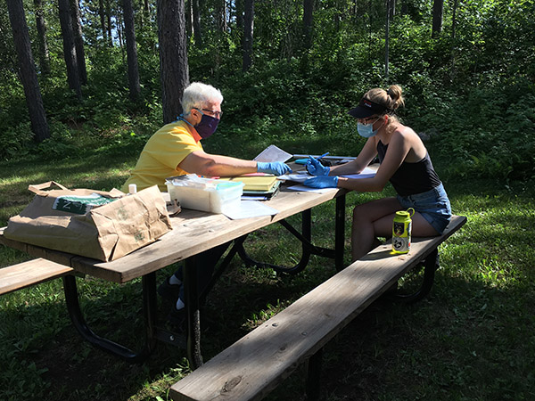 Two women with masks on sitting at a picnic table looking over old photos and documents
